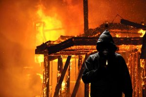 Arson Bonds Houston- Man in a hoodie and smoke-mask walking away from a burning building.