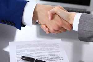Two men shaking hands over a signed agreement. This guy sure is happy he got fraud bonding services from Access Bonding!