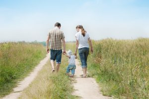 Fort Bend County Bail Bonds - family walking in a field with their toddler.