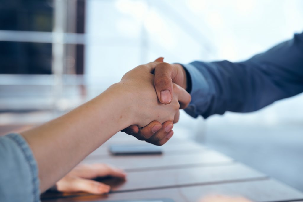 Surety Bond Houston - Two people shaking hands over a surety bond deal.